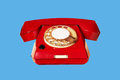 Outdated red phone closeup on blue background Royalty Free Stock Images