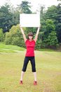 Outdoor asian girl with placard holding a white blank card at park Royalty Free Stock Photography