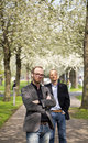 Outdoor business portrait of two partners one standing in front of the other posing on a footpath underneath blossoming trees Stock Photo