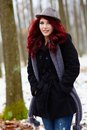 Outdoor closeup of young redhead a pretty woman in a forest hands in pockets Stock Image