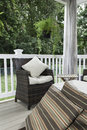 Outdoor decor seating area two resin wicker chairs sit on a covered deck they have cream colored cushions and pillows canvas Royalty Free Stock Images