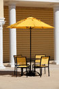 Outdoor dining table with yellow umbrella and chairs Stock Image