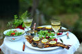 Outdoor dinner with grilled fish salad and coal roasted potatoes Royalty Free Stock Photo
