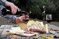 Outdoor eating with bread, cheese, sausage and red wine. Royalty Free Stock Photo