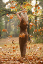 Outdoor in fall sexy woman brown dress autumn scene falling leafs and a beautiful blonde Royalty Free Stock Image