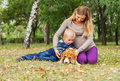 Outdoor family active leisure pregnant mother with her son fun playing with their pet in park Royalty Free Stock Photos