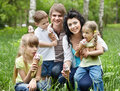 Outdoor family with kids on green grass. Royalty Free Stock Images