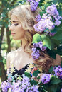 Outdoor fashion beautiful young woman surrounded by lilac flowers summer. Spring blossom lilac bush. Portrait of a girl blond