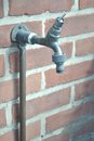 Outdoor faucet on a brick wall with a hose fitting attached. Royalty Free Stock Photo