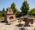 Outdoor fireplace and kitchen area a relaxing place to enjoy the dining this executive home enjoys Royalty Free Stock Photography