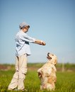 Outdoor fun portrait of cute lad playing with labrador on grass Stock Images