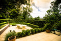 Outdoor garden terraces with a stone bench in a landscaped with formal trimmed hedges Stock Photo