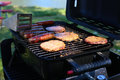 Outdoor grill with hamburgers, brats, and hot dogs Royalty Free Stock Photo