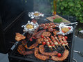 Outdoor grill with meat and potatoes assorted cooking on an Royalty Free Stock Image