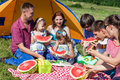 Outdoor group portrait of happy company having picnic near the tent in park and enjoying watermelon Royalty Free Stock Photo