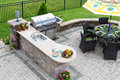 Outdoor kitchen and dining table on a paved patio Royalty Free Stock Photo