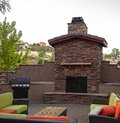 Outdoor kitchen fun a large stone fireplace along with a bbq and sofa s provide the perfect place for a party Stock Image