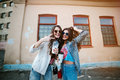 Outdoor lifestyle portrait of a pair of best friends pretty young girls wearing sunglasses, wearing a bright prey Royalty Free Stock Photo
