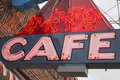 Outdoor neon cafe sign the vintage out doors lit colorful red and blue or restaurant food business building is aged with a cloudy Royalty Free Stock Image