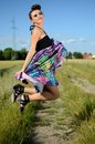 Outdoor photo of jumping model happy female young polish wearing colorful dress green fields and blue sky as background Stock Image
