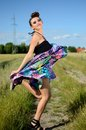 Outdoor photo of jumping model happy female young polish wearing colorful dress green fields and blue sky as background Royalty Free Stock Images