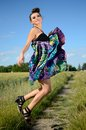 Outdoor photo of jumping model happy female young polish wearing colorful dress green fields and blue sky as background Stock Images
