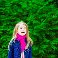 Outdoor portrait of an adorable laughing blond little girl wearing a jeans jacket and a pink scarf Stock Photo