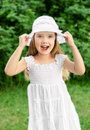 Outdoor portrait of adorable screaming little girl in white dress and hat Royalty Free Stock Images