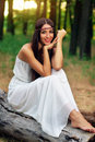 Outdoor portrait of beautiful hippie girl sitting on a dry log Stock Image