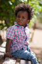 Outdoor portrait of a black baby sited on a bench cute boy Stock Photography