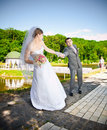 Outdoor portrait of bride pulling by hand resist groom Stock Photos
