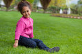 Outdoor portrait cute little african asian girl lying seated grass Stock Photos