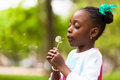 Outdoor portrait of a cute young black girl blowing a dandelion flower african people Stock Image