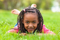 Outdoor portrait of a cute young black girl smiling african pe lying down on the grass and people Stock Photo