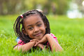 Outdoor portrait of a cute young black girl smiling african pe lying down on the grass and people Royalty Free Stock Image