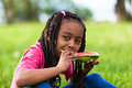 Outdoor portrait of a cute young black little girl eating waterm watermelon african people Stock Image