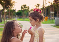Outdoor portrait of Little beautiful girls painting lips of pink Royalty Free Stock Photo