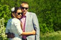 Outdoor portrait of loving couple young in smart clothes standing close together both wearing sun glasses with background trees Royalty Free Stock Photo