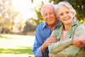 Outdoor portrait of loving senior couple holding hands smiling to camera Royalty Free Stock Photos