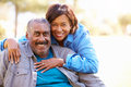 Outdoor portrait of loving senior couple looking at camera smiling Stock Images