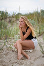 Outdoor portrait of melancholy and sad young pretty woman sitting on the sand near the sea alone Stock Photo
