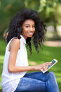 Outdoor portrait of a teenage black girl using a tactile tablet smiling african people Royalty Free Stock Images