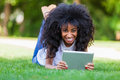 Outdoor portrait of a teenage black girl using a tactile tablet smiling african people Royalty Free Stock Image