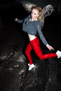 Outdoor portrait of young beautiful happy blond european lady posing on street at night. Model wearing stylish clothes red pants a Royalty Free Stock Photo