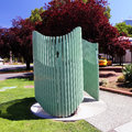 Outdoor public restroom a modern shape for men painted in green Stock Image