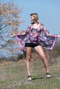 Outdoor shoot for fashion green field model is wearing a purple shirt shorts and heels upstanding show off her long legs full Stock Photo