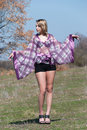 Outdoor shoot for fashion green field model is wearing a purple shirt shorts and heels upstanding show off her long legs full Royalty Free Stock Photography