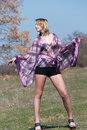 Outdoor shoot for fashion green field model is wearing a purple shirt shorts and heels upstanding show off her long legs full Stock Images
