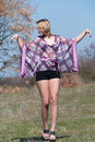 Outdoor shoot for fashion green field model is wearing a purple shirt shorts and heels upstanding show off her long legs full Stock Photos