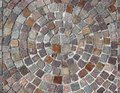 Outdoor stone flooring of porphyry cubes made with a round design, with circles that becomes larger starting from the center Royalty Free Stock Photo